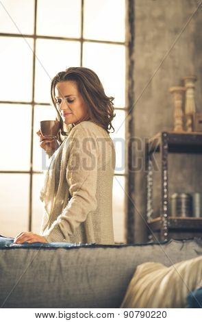 Brunette Holding Cup Of Coffee In Loft