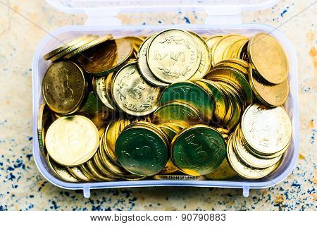 Indian 5 rupee coins kept in a plastic box on a blurred background