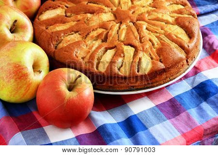 Freshly baked apple pie with apples in the background.