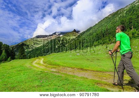 Mountaineer with poles on alpine trail, Austria