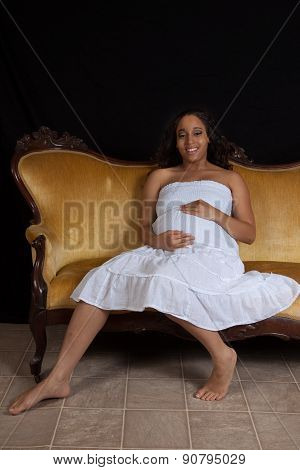 Pretty pregnant woman sitting on a couch