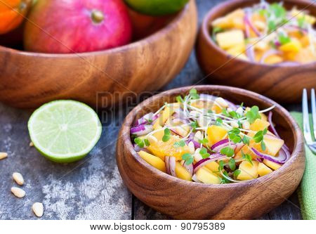 Vegetarian Salad With Mango Oranges And Red Onion On The Wooden Plate