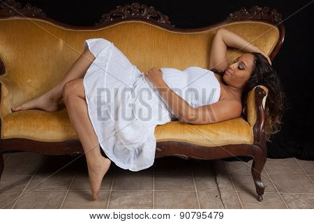 pregnant woman laying down on a bench