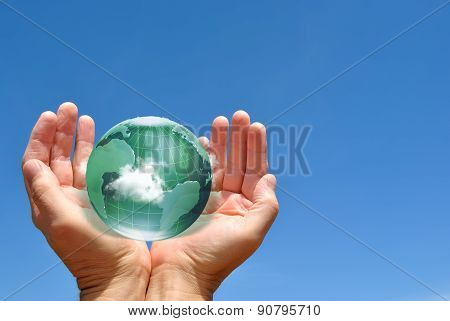 Globe In Human Hands Against Blue Sky