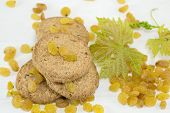 image of baked raisin cookies  - Integral cookies and yellow raisins with a large green flower on white - JPG