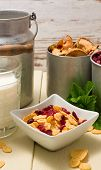 image of fruit bowl  - Vertical photo of square white bowl full of cornflakes with berries among glass of milk two cups with dried fruit green herbs and aluminum can - JPG
