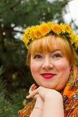 stock photo of flirty  - Cheeked Russian cheerful young woman in a wreath of fresh dandelion flirt flirty look - JPG