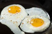 image of scrambled eggs  - Two scrambled eggs in black frying pan - JPG
