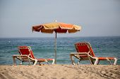 stock photo of dingy  - Faded and dingy lounger and umbrella at the beach - JPG