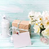 picture of text-box  - Background with colorful narcissus flowers candles box with present and empty tag for text on turquoise painted wooden planks - JPG