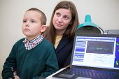 image of infirmary  - boy sits in mothers lap at a reception at the ophthalmologist - JPG