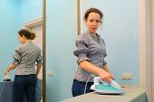 stock photo of jeans skirt  - young housewife in gray blouse and jeans was ironing in room - JPG