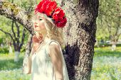 image of woman red blouse  - beautiful young gentle elegant young blond woman with red peony in a wreath of white blouse walking in the lush apple orchard - JPG