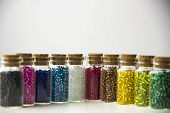 foto of beads  - Tiny glass bottles filled with beads of different colors - JPG
