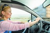 foto of driving  - Attractive adult woman safe and carefully driving car on suburban road - JPG