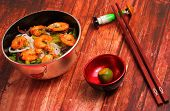 picture of rice noodles  - Vietnamese shrimp and rice noodles soup pho served on a wood table top - JPG