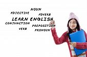 foto of verbs  - Young asian student in winter clothes learns English and write English material on whiteboard - JPG