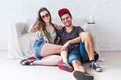 foto of mans-best-friend  - Friends girl and guy sitting on floor at home in summer jeanswear street urban casual style talking - JPG