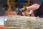 stock photo of man chainsaw  - Close up of male hands cutting trunk with chainsaw - JPG