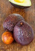picture of avocado  - Two ripe avocados and avocado core on an old rustic wooden plank - JPG