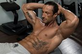 image of abdominal  - Muscular Mature Man Exercising Abdominals On Exercise Ball In Modern Fitness Center - JPG