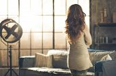 picture of comfort  - Seen from behind a brunette woman in comfortable clothing is standing in a loft living room looking out the loft window - JPG