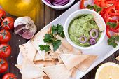 picture of nachos  - Guacamole in porcelain Bowl with mexican Tortilla Chips nachos and Ingredients - JPG