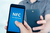 image of payment methods  - Hand holding smartphone with NFC technology  - JPG