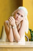 image of natural blonde  - Natural and beautiful blonde teen girl looking into camera with a mobile phone at a cafe - JPG