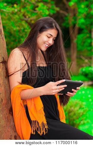 Teen Girl In Black Dress Outdoors Using Tablet Computer