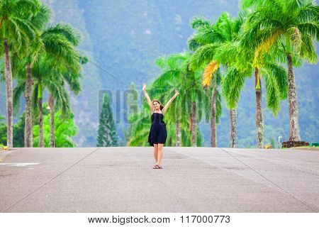 Teen girl walking along palm tree lined road arms raised overhead
