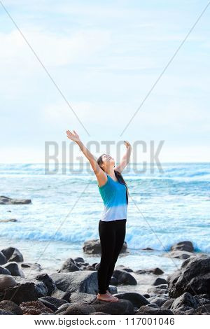 Teen Girl Standing On Rocky Beach Arms Raised, Praising God