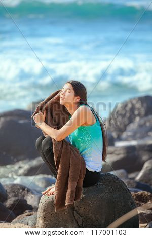 Teen Girl Sitting On Rocky Beach Shore Drying Off