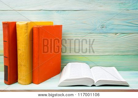 Open book, stack of colorful hardback books on wooden table. Back to school. Copy space for text