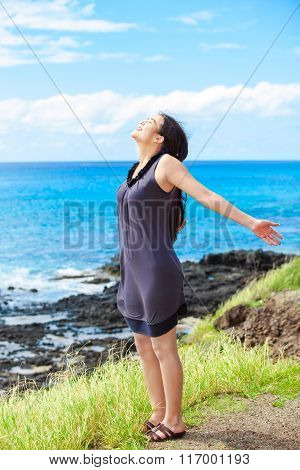 Biracial Teen Girl On Cliff, Arms Outstretched By Ocean