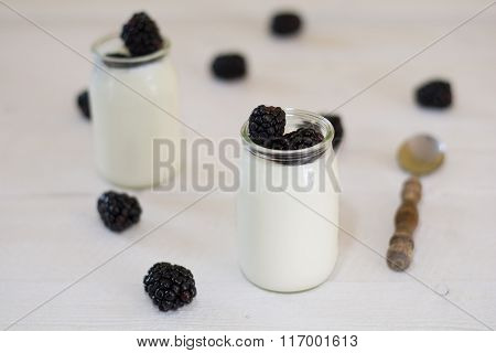 White Yogurt With mulberry On A Rustic Table