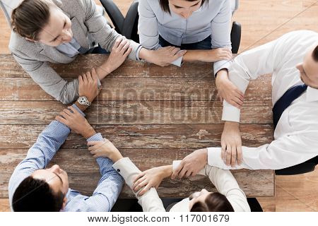 close up of business team holding hands at table