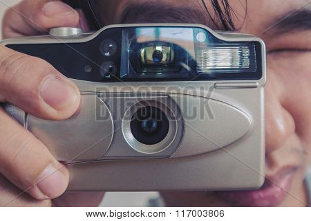 Vintage tone, close up a man taking photograph by vintage film camera