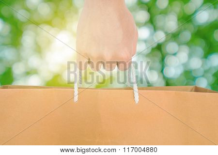 Hand holding reuse paper bag, on green Bokeh and bright yellow light background
