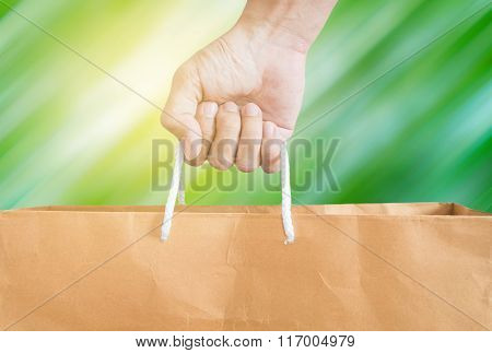 Hand holding reuse paper bag, on green motion blur and bright yellow light background