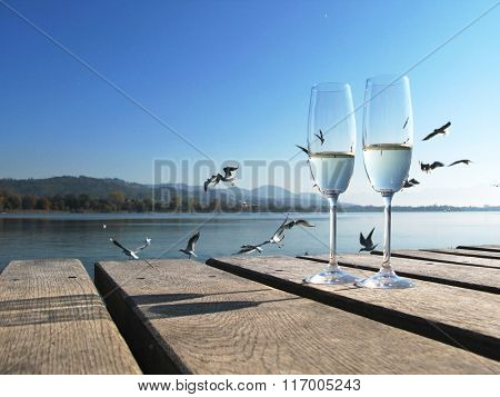Two champaign glasses against a lake