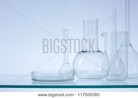 Assorted empty laboratory glassware, test-tubes. Blue tone medical background. Copy space for text.
