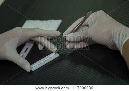 Lab tech using tweezers to remove specimen