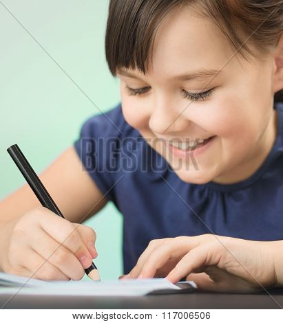 Cute cheerful child drawing using pencil while sitting at table, closeup