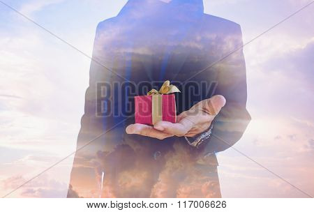 Double exposure, vintage tone, businessman with gift box on hand, and beautiful fantasy sky