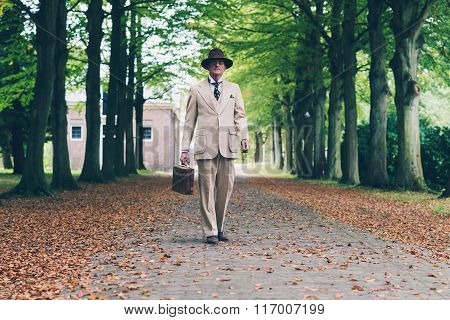 Senior Man With Hat And Suit Holding Suitcase. Walking In Avenue.