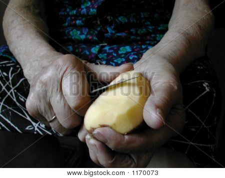 Old Lady Cleaning Potatoes