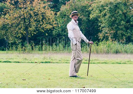 Dandy Standing With Cane On Lawn In Garden.
