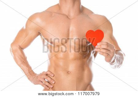 Bodybuilding And Health: Handsome Strong Bodybuilder Holding A Paper Card Red Heart Isolated On A Wh