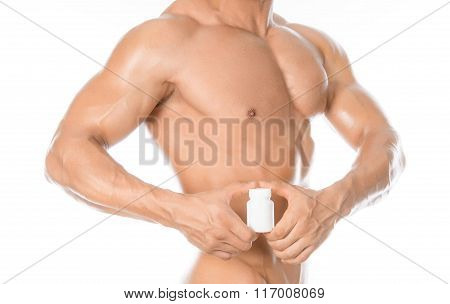 Bodybuilding And Chemical Additives: Handsome Strong Bodybuilder Holding A White Jar Of Pills On Whi